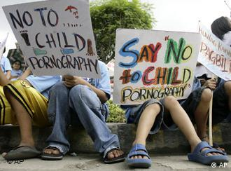 Children holding signs that read Say No to Child Pornography