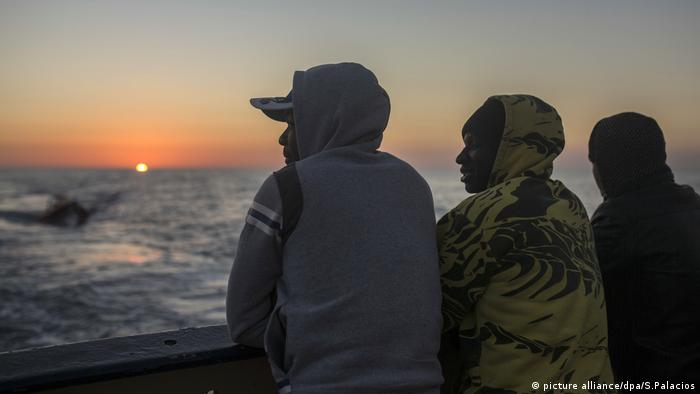 Three migrants staring out at the Mediterranean from the ship that rescued them