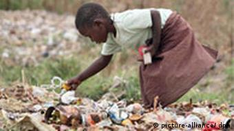 A young girl scavenges for food in a rubbish dump in Zimbabwe
