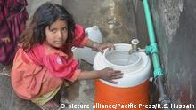 A girl fills a bottle in Pakistan