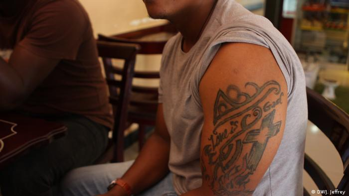 Young man with religious tattoo on his arm