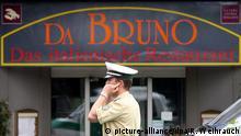 15.08.2007 - Ein Polizist telefoniert am 15.08.2007 in Duisburg am Schild des Restaurants Da Bruno in der Nähe des Tatortes, wo am Morgen fünf Menschen erschossen und ein Mann schwer verletzt aufgefunden worden waren. Mehr als sechs Jahre nach den Mafiamorden von Duisburg ist einer der Täter in Italien zu lebenslanger Haft verurteilt worden. Das Urteil gegen den 42-jährigen Sebastiano Nirta wurde bereits amSonntag vom Geschworenengericht im kalabrischen Locri gesprochen, wie die Nachrichtenagentur Ansa berichtete. Im August 2007 waren inDuisburg sechs Italiener vor einem Restaurant auf offener Straße erschossen worden. Auslöser soll eine Fehde zwischen zwei Mafia-Clans gewesen sein. Foto: Roland Weihrauch dpa/lnw +++(c) dpa - Bildfunk+++   Verwendung weltweit