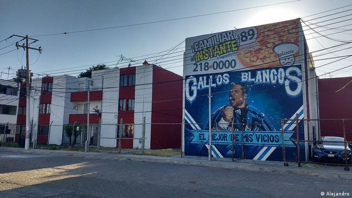Fachada de una casa mexicana con un mural del club de fútbol Gallos Blancos.
