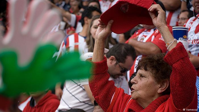 Una mujer de edad avanzada apoya a su equipo de fútbol en el estadio.