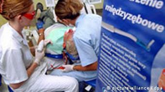 Zahnärztin und Assisentin bei der Behandlunge eines Patienten in einer Zahnklinik Szczecin (Foto: dpa)
