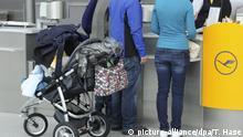 Fluggäste mit einem Kinderwagen werden am 04.06.2013 in München (Bayern) am Flughafen an einem der Schalter der Fluggesellschaft Lufthansa bedient. | Verwendung weltweit