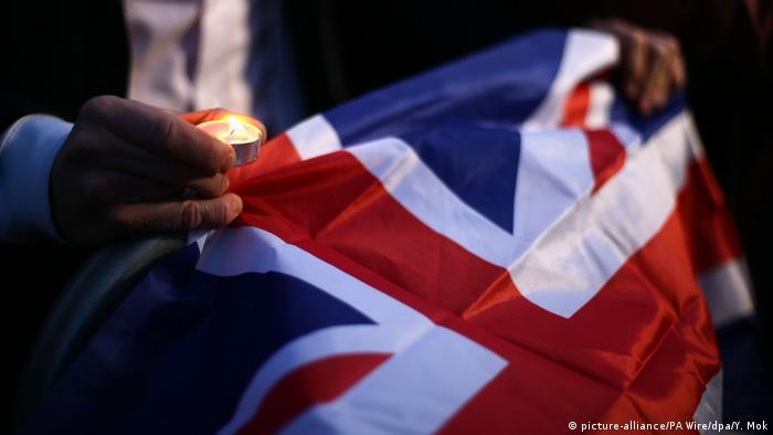 Человек держит в руке свечку и британский флаг