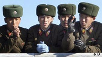 North Korean soldiers watch the South Korean side at the border village of the Panmunjom