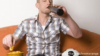 Mann sitzt mit Chips, Bier und Fußball auf dem Sofa
