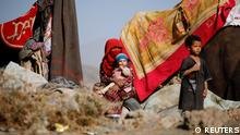 A woman sits with her children near their tent at a camp for internally displaced people in Dharawan, near the capital Sanaa (REUTERS)
