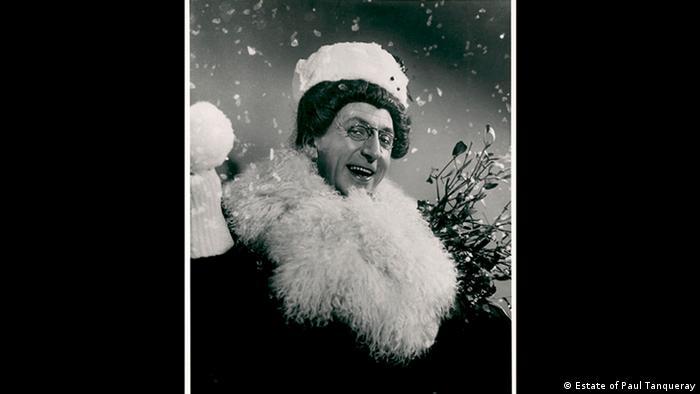 La personificación de los roles femeninos por parte de hombres tiene una larga tradición en Gran Bretaña. Recién a partir de 1660 las mujeres acceden al escenario como actrices. Douglas Byng – aquí retratado en una fotografía de Paul Tanqueray – era abiertamente gay, un famoso Drag Queen y cantante. En sus canciones él no escatimaba en alusiones sexuales y dobles sentidos.