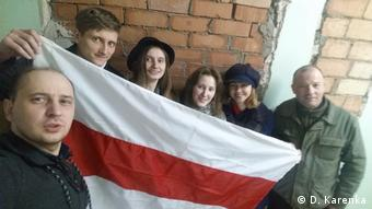 Антон Логвинец и его сторонники возле больницы держат бело-красно-белый флаг