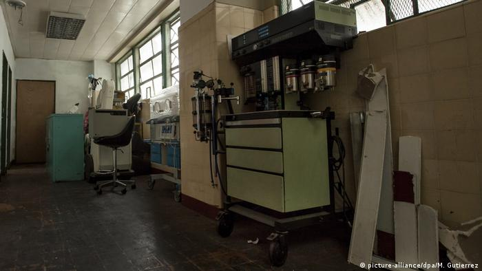 A dim hallway, with medical old-looking equipment and small windows.