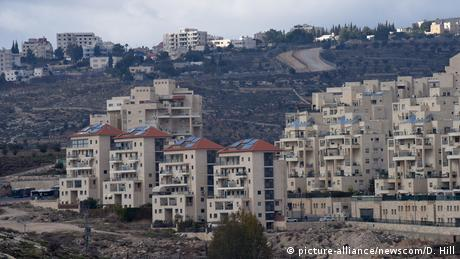 Apartment houses stand in desert land in an Israeli settlement while Palestinian houses stand atop a hill in the background (picture-alliance/newscom/D. Hill)