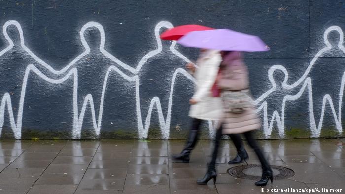 Frauen in Daunenjacken und Regenschirm laufen die Straße entlang, im Hintergrund ist ein Graffiti mit Strichmännchen zu sehen, die sich an der Hand halten (Foto: picture-alliance/dpa/A. Heimken)