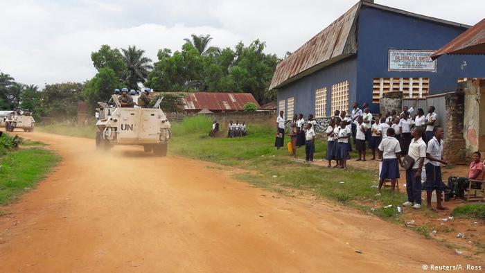 A MONUSCO convoy drives by as school children watch