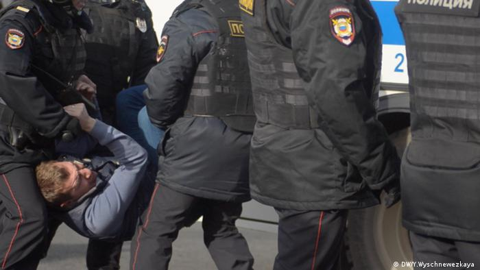 Полицейские тащут задержанного в автозак