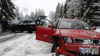 Two smashed cars stand on a snow-covered road
