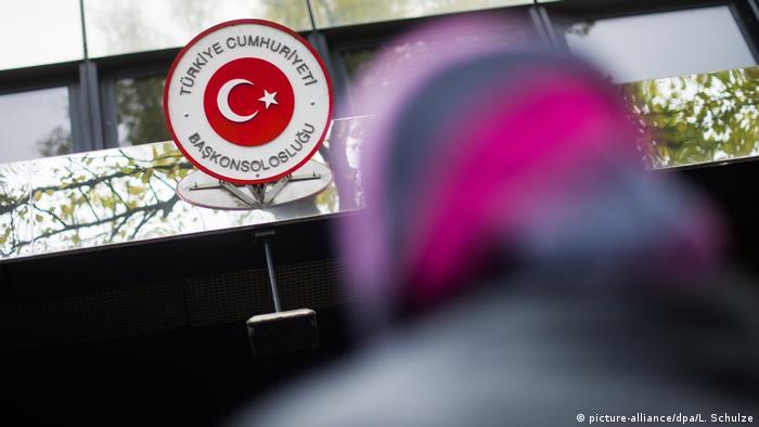 Женщина в платке смотрит на турецкий консулат в Берлине