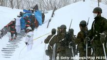 Firefighters carry someone from the site of an avalanche in Nasu town (Getty Images/AFP/JIJI PRESS)