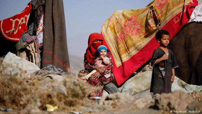 Una mujer y dos niños en un campo de refugiados en Yemen.