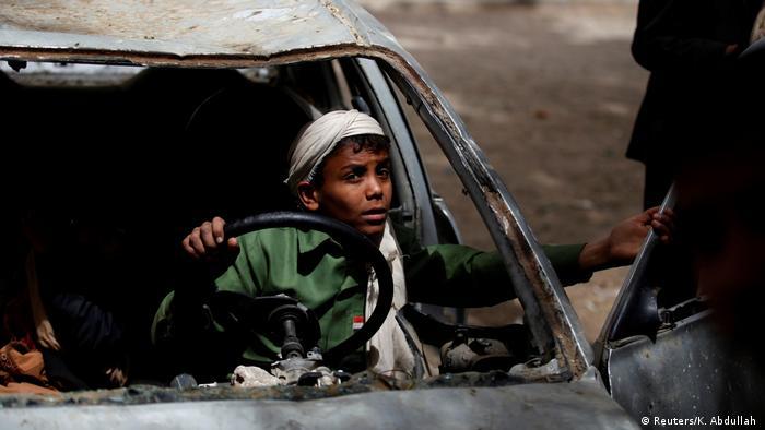 Un niño juega en un coche quemado en la capital yemení.