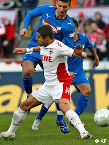 Cologne's Youssef Mohamad, left, challenges for the ball with Hoffenheim's Vedad Ibisevic