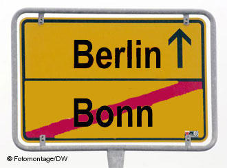 A city sign with the word Bonn crossed out at the bottom and Berlin with an arrow leading to it on top