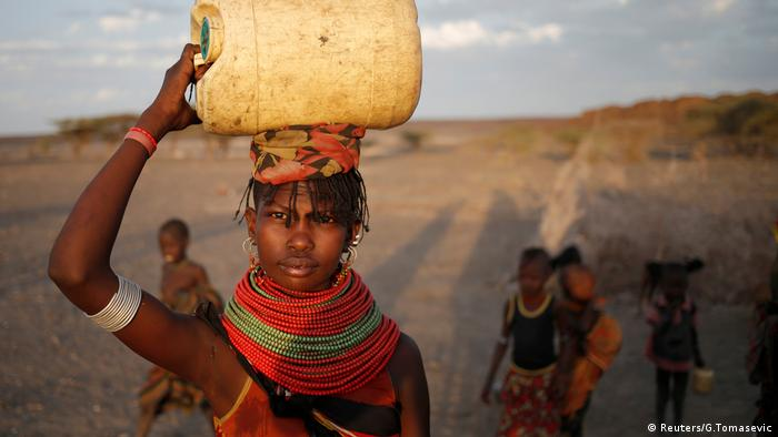 A woman carries a water canister in a village near Loiyangalani, Kenya