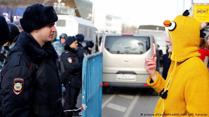 Демонстрант снимает полицейского на камеру смартфона