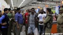 Indian police and onlookers surrounding African nationals at a shopping mall in Greater Noida. (Getty Images/AFP)