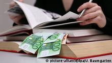 DEUTSCHLAND, BONN, 01.02.2005, Frau arbeitet in Büchern, in denen Euro Geldscheine stecken. Symbol: Studiengebühren, Studienfinanzierung, Studienkredit, Stipendium, BAFÖG, Lernmittelfreiheit, etc. | Keine Weitergabe an Wiederverkäufer.