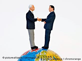 People shaking hands atop a globe