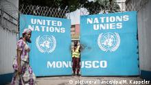 A woman walks by the gates of MONUSCO headquarters in DRC. (picture-alliance/dpa/M. Kappeler)