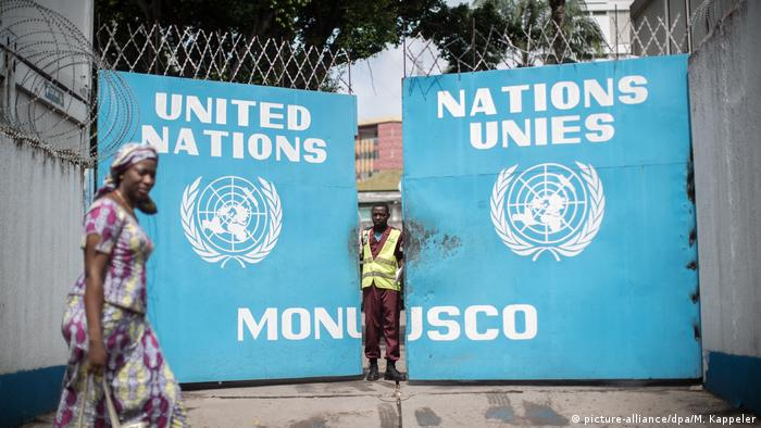 A woman walks by the gates of MONUSCO headquarters in DRC.