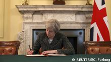 British Prime Minister Theresa May in the cabinet office signs the official letter to European Council President Donald Tusk invoking Article 50 and the United Kingdom's intention to leave the EU on March 28, 2017 in London, England. After holding a referendum in June 2016 the United Kingdom voted to leave the European Union, the signing of Article 50 now officially triggers that process. REUTERS/Christopher Furlong/Pool TPX IMAGES OF THE DAY