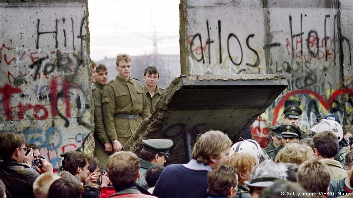 Soldiers are on one side of an open section of the Berlin Wall, civilians at the other