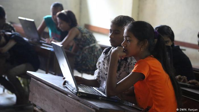 Girls share laptops in coding class