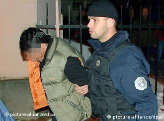 A man is being led away by a Kosovo police officer