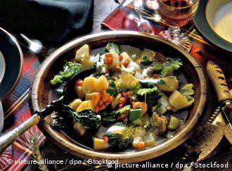 Ein Suppenteller, in dem ein Steckrübeneintopf aus verschiedenen Gemüsen und Schweinefleisch ist, mit einem Löffel darin
