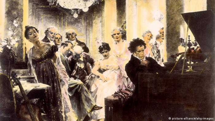 Ludwig van Beethoven playing on a piano, with well-heeled men and women standing behind him (Photo: picture-alliance/akg-images).