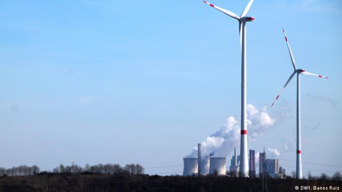 Wind turbines with coal plant in background