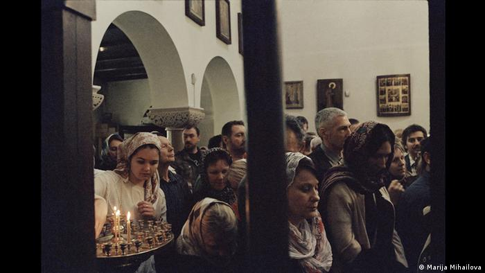 Women with covered heads in church, lighting candles (Marija Mihailova)