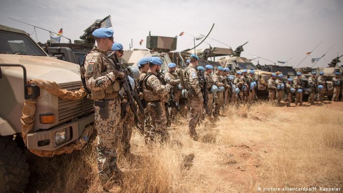 UN blue helmets line up against a convoy of vehicles