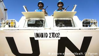 Two blue-helmeted UN soldiers standing in an armored vehicle Darfur.