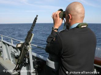 A German naval soldier on the frigate Brandenburg looks through binoculars at the open sea