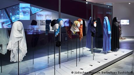 Κοντή ή μακριά μαντίλα, στερεωμένη στην κόμη ή δεμένη γύρω από τον λαιμό. Τι σημαίνουν οι παραλλαγές της γνωστής μουσουλμανικής μαντίλας; Μία έκθεση στο Εβραϊκό Μουσείο του Βερολίνου εξηγεί από ποια θρησκευτική ομάδα και ποια περιοχή προέρχεται η κάθε μαντίλα. Για πολλές πιστές μουσουλμάνες η μαντίλα σημαίνει υπακοή στους θεμελιώδεις κανόνες του Ισλάμ.