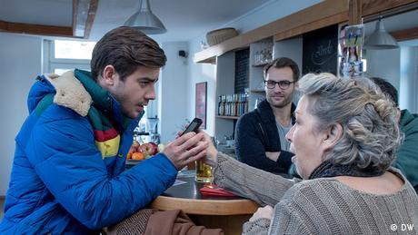 Eine ältere Frau zeigt einem jungen Mann ihr Smartphone.