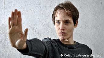 Symbolbild: Ein junger Mann streckt in abwehrender Geste den rechten Arm nach vorne