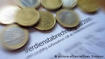 Geldmünzen auf einer Gehaltsabrechung symbolisieren die Forderung der Linken nach finanziellen Entlastungen für Bedürftige. Foto: picture-alliance